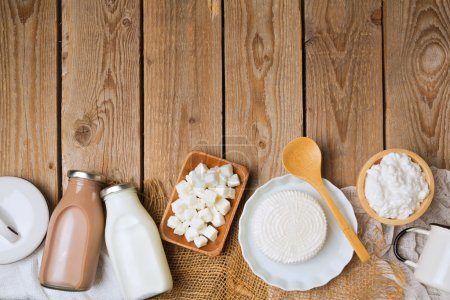 Photo for Milk bottles and cheese on wooden rustic background. View from above. Flat lay - Royalty Free Image