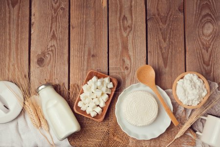Photo for Milk bottle and cheese on wooden table. Healthy eating concept. View from above. Flat lay - Royalty Free Image