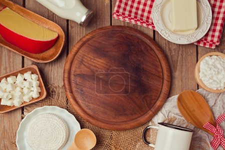 Photo for Wooden board with milk and cheese. Place for text. Healthy eating concept. View from abobe. Flat lay - Royalty Free Image