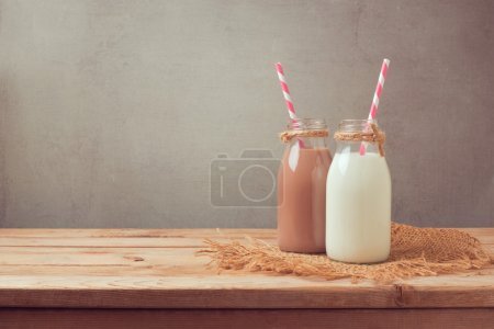 Photo for Milk bottle and chocolate milk bottle on wooden table. Healthy eating concept - Royalty Free Image