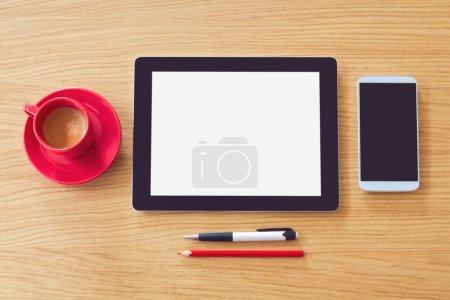 Photo pour Tablette avec écran vierge et smartphone avec tasse de café sur table en bois. Bureau maquette. Vue d'en haut - image libre de droit