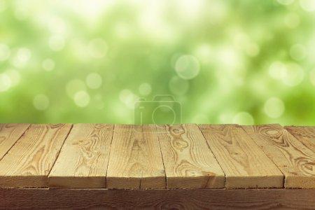 Foto de Mesa de vacío deck de madera con fondo de follaje bokeh. listo para montaje de la exhibición de productos. - Imagen libre de derechos