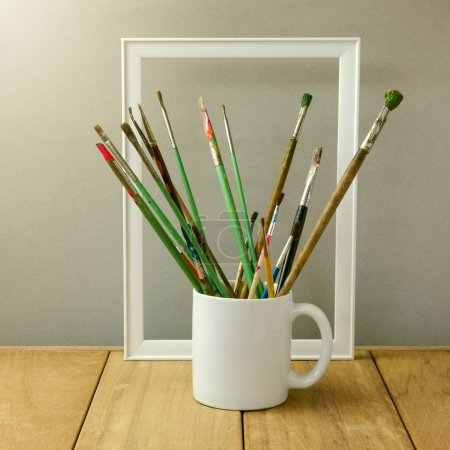 Photo for Painter brushes in white cup on wooden table. Cup for logo display mock up - Royalty Free Image