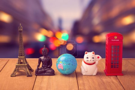 Photo for Travel around the world concept. Souvenirs from around the world on wooden table over city bokeh background - Royalty Free Image