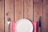 Wooden table with empty plate