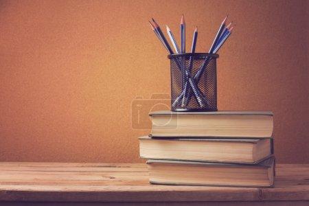 Photo pour Vieux livre avec des crayons sur la table en bois. Beaucoup d'espace de copie - image libre de droit