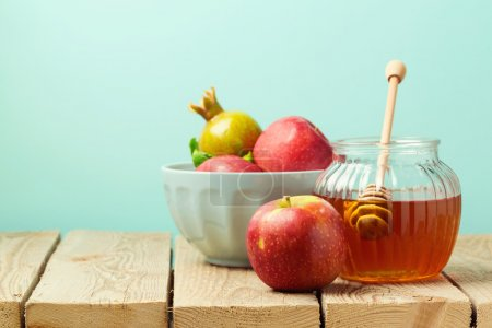 Apple and honey on wooden table