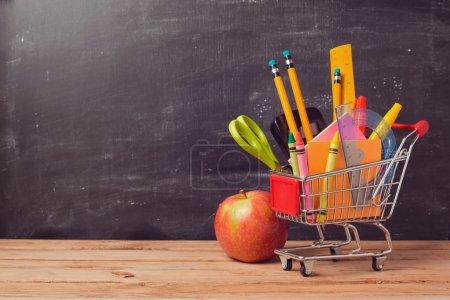 Photo for Shopping cart with school supplies over chalkboard background - Royalty Free Image
