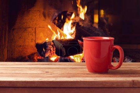 Photo pour Tasse rouge au-dessus de la cheminée sur la table en bois. Concept de vacances hiver et Noël - image libre de droit