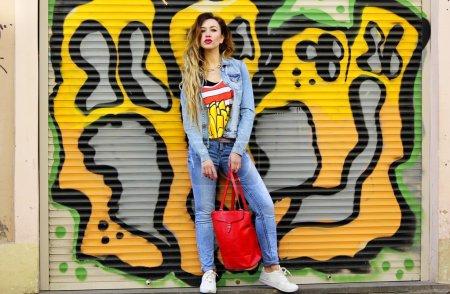 woman in denim clothes against graffiti wall