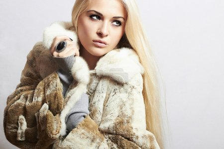Young beautiful woman in fur. winter style.pretty girl. Beauty blond Model Girl in Mink Fur Coat.lady with big ring