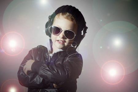 Little deejay. funny little boy in sunglasses and headphones.smiling child listening music in headphones. DJ. disco lights