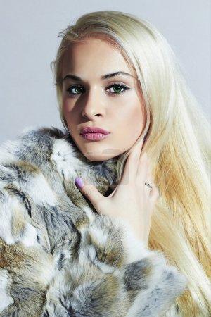 Beautiful blond woman in fur.winter fashion portrait.Beauty blond Model Girl in Rabbit Fur Coat. Woman in Luxury Fur Jacket
