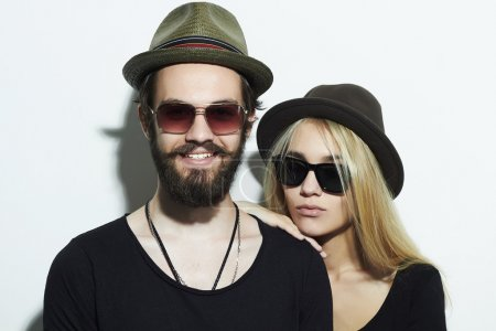 beautiful happy couple in hat wearing trendy glasses together. Hipster boy and girl. Bearded young man and blonde in sunglasses