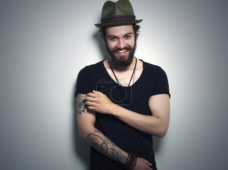 Photo for Fashion Portrait of young bearded man. Smiling Hipster boy.handsome man in hat.Brutal bearded boy with tattoo - Royalty Free Image