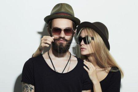 Photo pour Beau couple heureux en chapeau portant des lunettes à la mode ensemble. Hipster souriant garçon et fille. Jeune homme barbu et modèle blonde en lunettes de soleil - image libre de droit