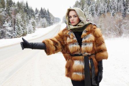 Photo pour Belle jeune fille dans un manteau de fourrure en attente pour la voiture sur une route d'hiver dans les forest.young femme à la mode manteau de fourrure, gants de cuir et écharpe. temps de neige - image libre de droit