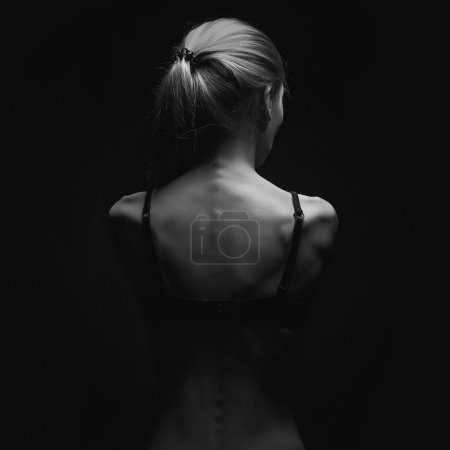 Sad woman with naked back over black background.sexy body girl