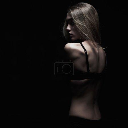 Photo pour Tristesse jeune femme avec dos nu sur fond noir. monochrome sombre portrait de corps sexy fille - image libre de droit