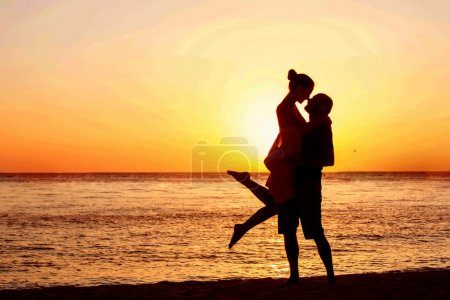 Romantic couple on the beach at colorful sunset on background