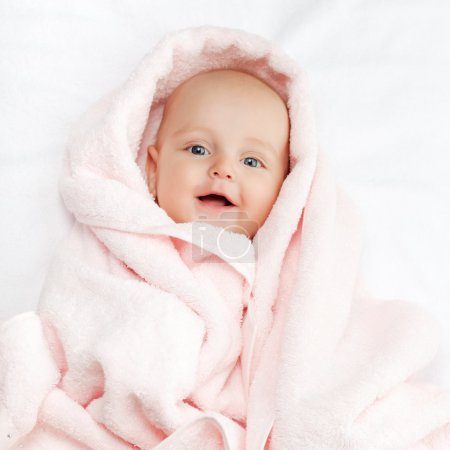 Photo for Caucasian baby boy covered with pink towel joyfully smiles at camera - Royalty Free Image