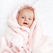 Caucasian baby boy covered with pink towel joyfully smiles at ca