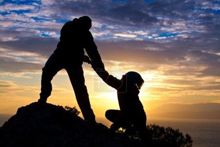 Photo pour Silhouette de couple au sommet de la montagne à la mer au coucher du soleil - image libre de droit