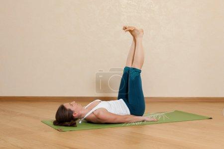 Caucasian woman is practicing yoga at studio (salamba prasarita