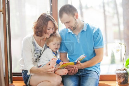 Happy family sitting on a windowsill and read a book.