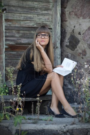 Beautiful girl in black glasses and a collection of poems