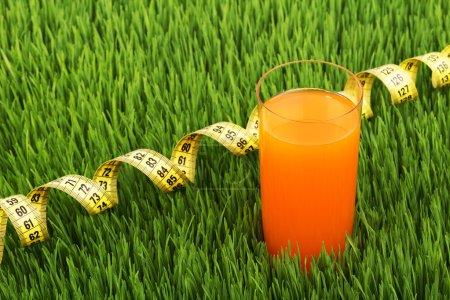 Photo pour Un verre de jus sur une herbe verte, la saine alimentation, le champ de blé vert, compteur embobinés, verrerie sur l'herbe, suivre la figure, un verre de jus d'orange, un compteur pour mesurer le corps, un compteur de chiffon à l'échelle. - image libre de droit