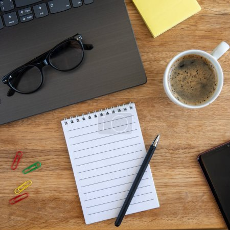 Laptop with glasses, coffee cup, notebook, sticky ...