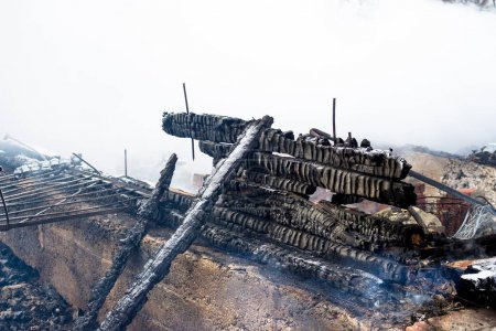 Burnt walls of a wooden house after a fire. Charre...