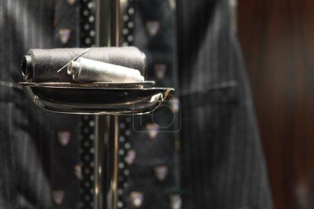 Photo pour Aiguille et fil sur pied avec gilet et cravate en arrière-plan - image libre de droit