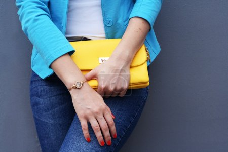 The fashionable young woman  holding yellow clutch