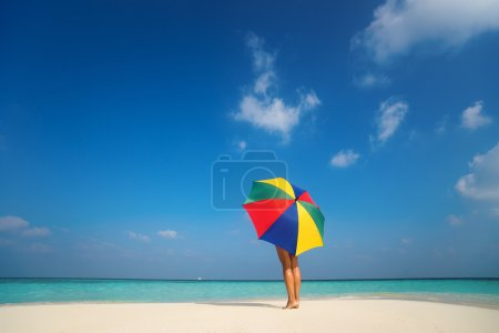 Girl with an colorful  umbrella on the sandy beach