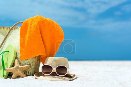 Summer beach bag with starfish,towel,sung lasses and flip flops on sandy beach