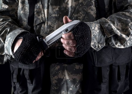 Photo for Military man with a knife in a hand close up on the black background - Royalty Free Image