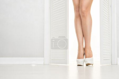 Women leg in white shoe looks out of the open door