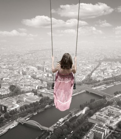 Young woman on a swing on the Paris town backround