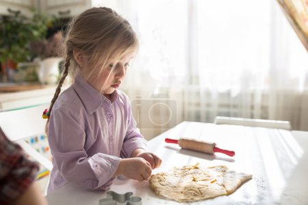 little Caucasian girl with pigtails makes the cookies from the d