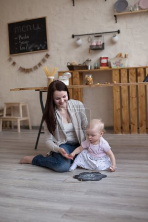 Young mother and toddler daughter drawing  black board and chalk