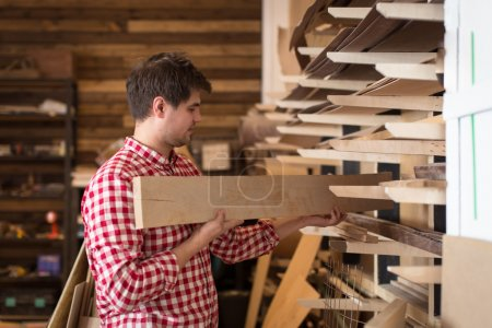 carpenter chooses a wooden board, joiner's shop, the concept of