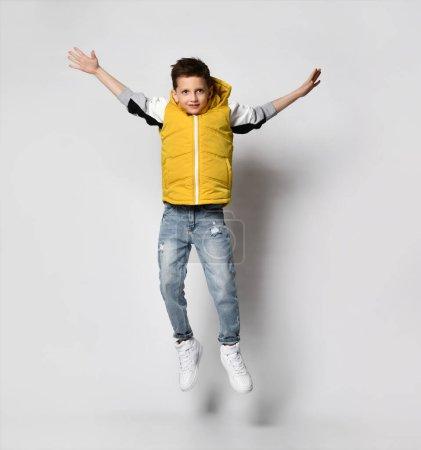 Photo pour Adolescent gars dans un gilet jaune doudoune sans manches avec une capuche et un jean s'amuse et a sauté haut sur un fond blanc - image libre de droit