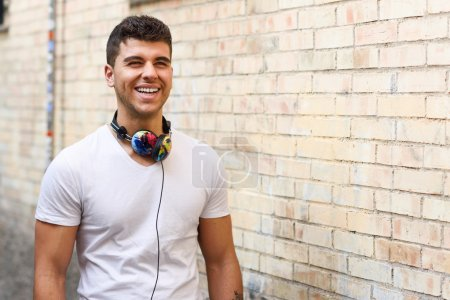 Young man in urban background listening to music with headphones