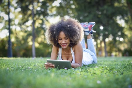 Photo for Young black woman with afro hairstyle laying on grass in urban park looking at her tablet computer. Mixed girl wearing casual clothes. - Royalty Free Image