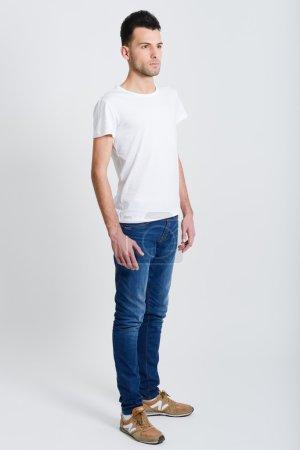 Photo pour Portrait d'un jeune homme intelligent et sérieux debout sur fond blanc - image libre de droit