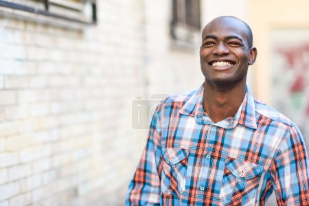 Photo for Portrait of black man very happy, smiling in urban background - Royalty Free Image