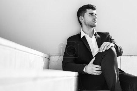 Photo pour Jeune homme d'affaires près d'un immeuble de bureaux moderne portant un costume noir et chemise blanche assis sur le sol. Homme aux yeux bleus en fond urbain - image libre de droit