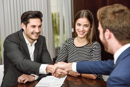 Photo pour Smiling young couple shaking hands with an insurance agent or investment adviser - image libre de droit
